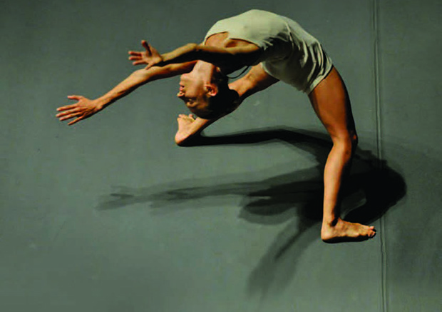 dancer with very little hair, very little clothing, reaches back. Her hands are almost to the floor behind her but she sustains a pose that brings all bodily strength and discipline to the fore.